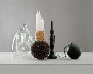 Photographie proposée par d'Anne Veaute pour illustrer le confinement : objets posés sur une table blanche : un bilboquet, une cloche en verre, un bouquet de bougies